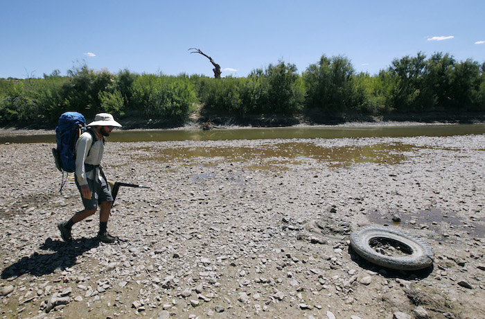 TRUTH OR CONSEQUENCES, NM - Colin McDonald walks a dry river bed near Truth or Consequences, New Mexico. AUGUST 30, 2014. CREDIT: Erich Schlegel/Disappearing Rio Grande Expedition