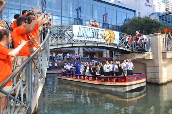 """The delegation barge makes its way through the Rivercenter Lagoon during the """"Bring It"""" River Rally for the NCAA Committee delegation. Photo by Iris Dimmick."""