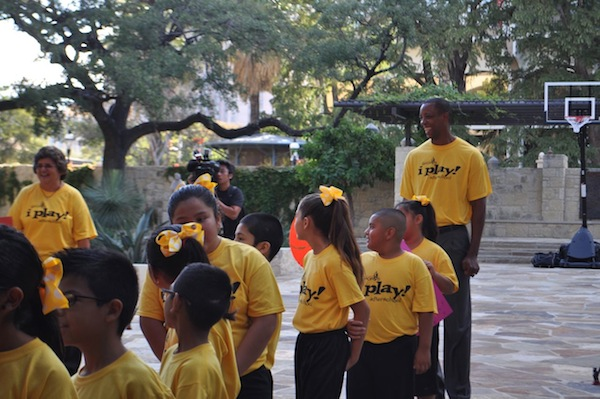 Sean Elliot and a troop of children participating in I Play, Afterschool –a program of San Antonio Sports – gather to greet the NCAA Committee delegates. Photo by Iris Dimmick.