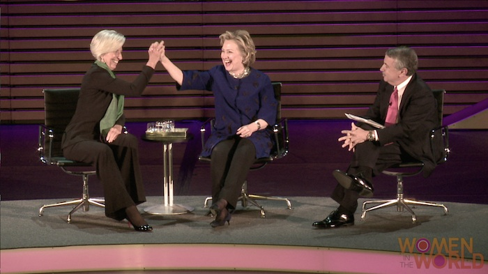 Christine Lagarde and Hillary Rodham Clinton join hands during an interview moderated by Thomas L. Friedman of the New York Times for Women in the World. Courtesy photo.
