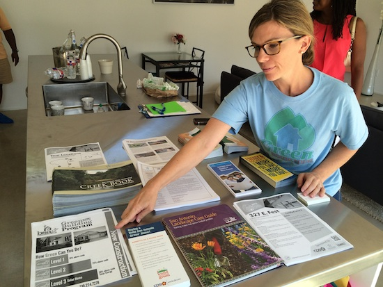 Stephanie Pittman, a Build San Antonio Green volunteer, displays informational brochures at a green home on Fest Street. Photo by Katherine Nickas.