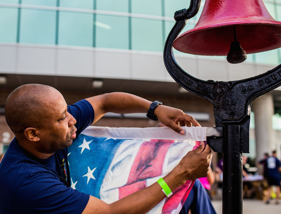A firefighter hangs an American Flag during the second annual San Antonio 110-9/11 Memorial Climb. Photo by Scott Ball.