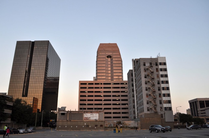 Section of Downtown San Antonio skyline from left: One Riverwalk Place, Bank of America Plaza (parking garage in foreground), and the vacant Hedrick building. Photo by Iris Dimmick.