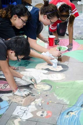 Members of nonprofits, universities, and schools work together to create unique chalk creations. Photo by Francisco Cortes.