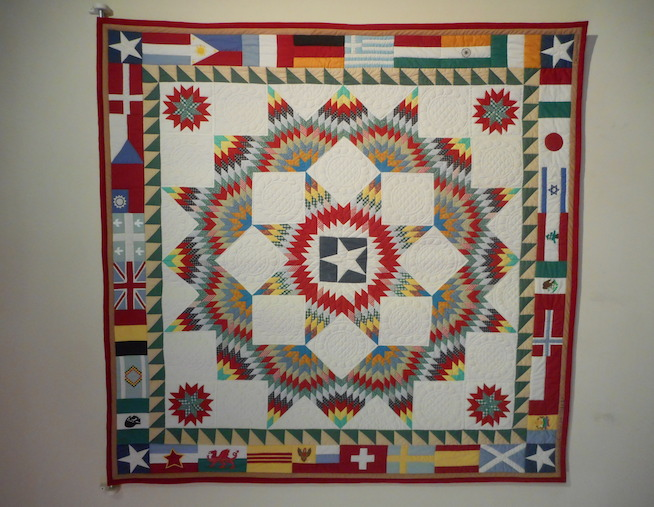 Chris Moroney painted a quilt existing only in his mind. His artwork featured a border of flags symbolizing Texas' rich heritage and was selected for the 1983 Texas Folklife Festival poster. The Greater San Antonio Quilt Guild transformed the painting into reality. It hangs in the foyer of the ITC. Photo by Don Mathis.