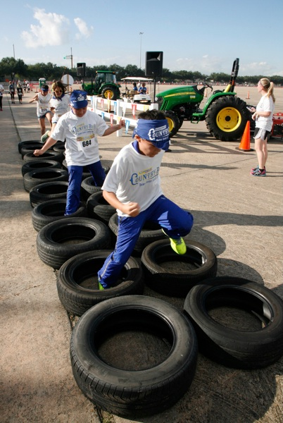 Runners jump through tires at the Corner Store Country Run in Houston. Photo by John Everett.
