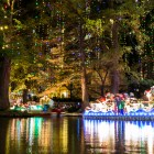 A float parks under trees draped with Christmas lights at the Holiday River Parade. Photo by Scott Ball.