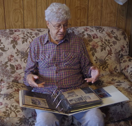 Kenneth Dominique sorts through photo albums. Photo by Juan Garcia.
