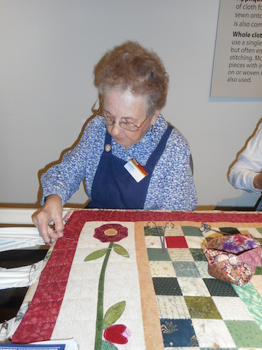 Kay Allison quilting the border of a Cottage Grove design. Photo by Don Mathis.