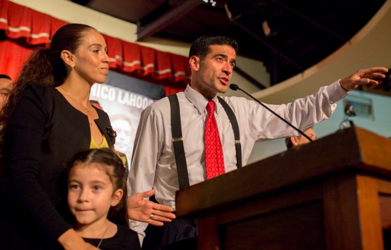 """Nicholas """"Nico"""" LaHood addresses supporters on election night with his wife, Davida, and daugher Maya, 5. Photo by Scott Ball."""