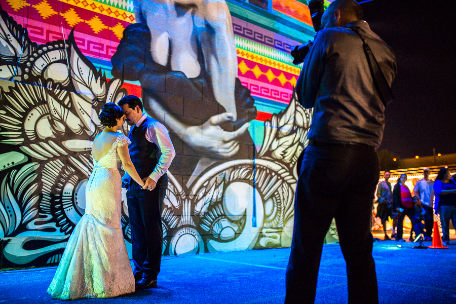 A couple has wedding photos taken in front of the mural created by Nik Soupe, Shek Vega, and Cris Montoya during the 2014 Luminaria. Photo by Scott Ball.