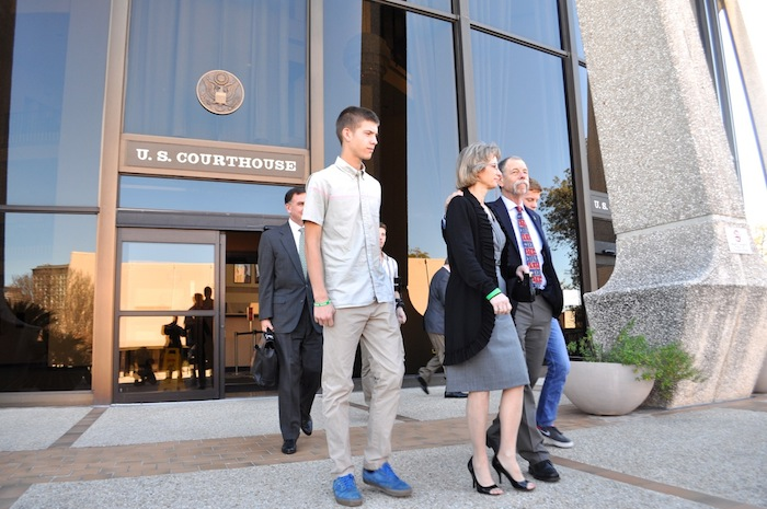 William Redus (left) walks out of the federal courthouse with his parents, Valerie and Mickey. Photo by Iris Dimmick.