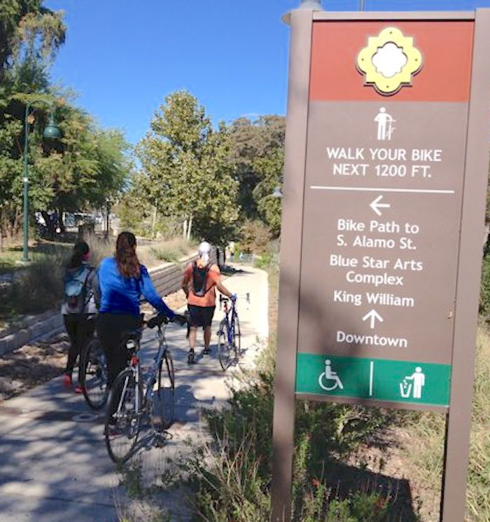 Cyclists obey signage to walk their bikes on a stretch of the Eagleland Reach. Photo by Robert Rivard.