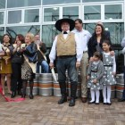 Alamo Beer Company Founder and President Eugene Simor stands with his family and historic reenactor Mike Waters as Waters cuts the ceremonial ribbon to mark the beginning of production.
