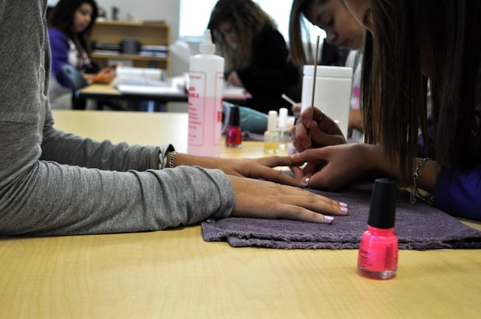 Cosmetology students practice painting each others' nails at Brackenridge High School's Career and Technology Education center. Photo by Iris Dimmick.