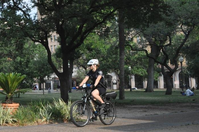 An SAPD bike patrol officer rides through Travis Park. Photo by Iris Dimmick.