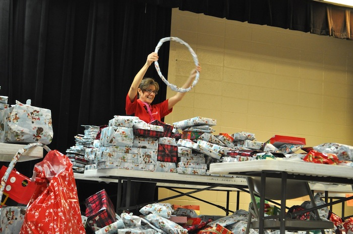 A volunteer finds the perfect gift to add to a family's pile of presents at the Family Service Association. Photo by Iris Dimmick.