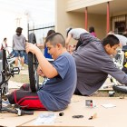Kids assemble new bikes during the Earn-A-Bike Christmas at Cassiano Homes. Photo by Rachel Chaney.