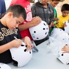 Kids decorate their new helmets during the Earn-A-Bike Christmas at Cassiano Homes. Photo by Rachel Chaney.