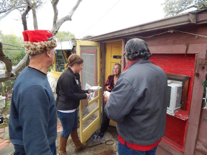 H-E-B Public Affairs Specialists Lacey Kotzur and Danny Flores deliver a meal to a senior in her home on Wednesday as part of the Feast of Sharing tradition. Courtesy photo