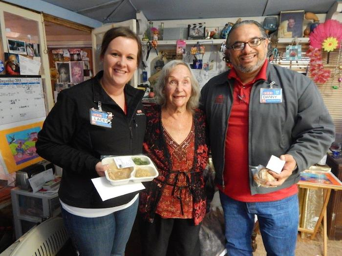 H-E-B Public Affairs Specialists Lacey Kotzur and Danny Flores stand with a recipient of one of the Feast of Sharing home-delivered meals. Courtesy photo