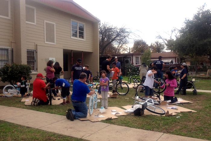 The lawn in front of Jireh House is a hot bed of activity on day one of the Earn-a-Bike Christmas program. Photo by Lily Casura.