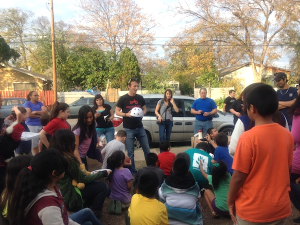 Cristian Sandoval talks helmet safety with the crowd, at the Earn-a-Bike Christmas program. Photo by Lily Casura.