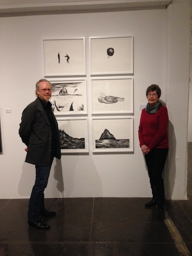 Janet Flohr and Gary Nichols stand with a series of lithographs by Robyn O'Neil. Photo by Wendy Weil Atwell.