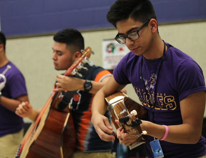 Jude Perez (right) plays an ornate rhythm on vihuela as his partner Alexis Reyes (left) plucks the guitarron beside him. As the heartbeat of the group, the two are required to listen and work in harmony with each other, hence being called an armonia section. Photo by Amanda Lozano).