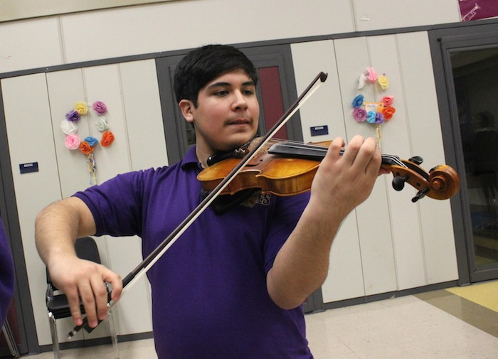 Standing tall and proud, Raymond Nieto focuses on playing violin for Mariachi Aguila. Photo by Amanda Lozano.