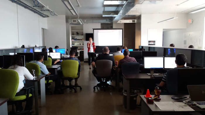 """Webhead employees listen to a presentation at Webhead HQ in the """"Pit."""" Photo courtesy of Webhead."""