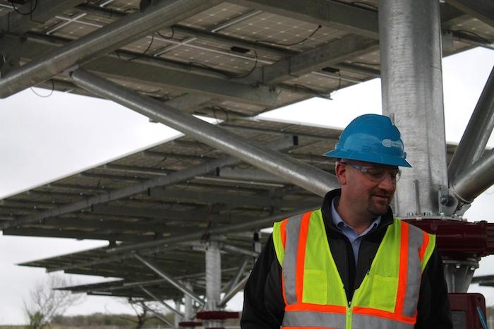 Dennis Brennan, operations and maintenance manager at Alamo 3 peeks down at a solar panel. Photo by Amanda Lozano.