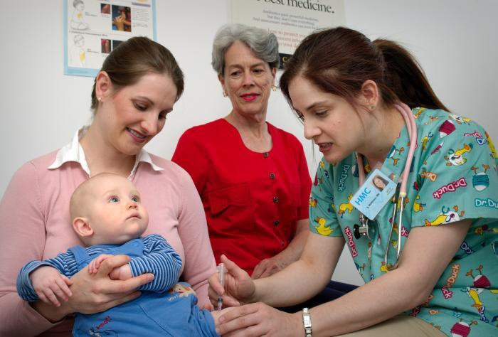 Held by his mother, this infant receives immunization in his left thigh muscle. Photo courtesy of the CDC.