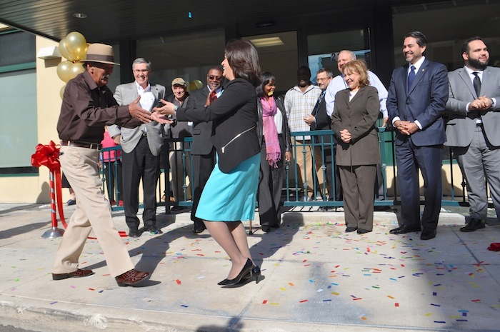 President and CEO Lourdes Castro Ramírez dances with long-time resident Esmael Suarez at the grand opening of SAHA's Lofts at Marie McGuire. Photo by Iris Dimmick.