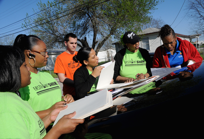 Deborah Bell, homeownership manager for SAHA, strategizes with volunteers during the EastPoint Shine Paint-A-Thon. Photo by Kristian Jaime.