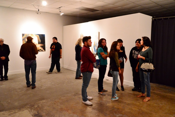 Onlookers view Yenifer Gaviña's art at ® Space. Photo by Page Graham.