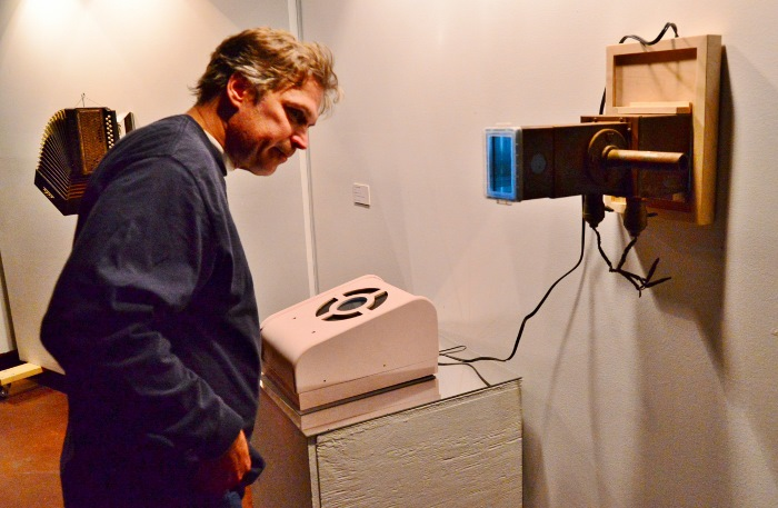 Patrick Zeller checks out artworks by Andy Benavides. Photo by Page Graham.