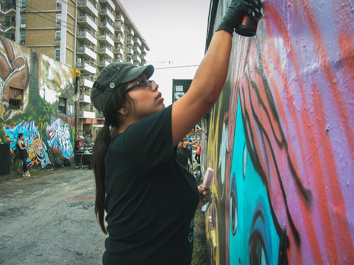 Rabbit Rye put the finishing touches on her wall mural. This photo was taken during a local festival called Content Under Pressure. Photo by Blue Hernandez.