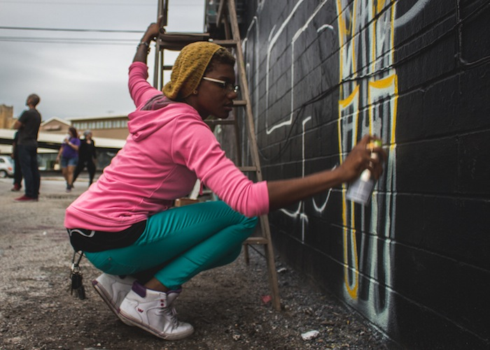 The artist known as Roshi K works to finish her wall mural during the Content Under Pressure festival that was held in San Antonio. Photo by Blue Hernandez.