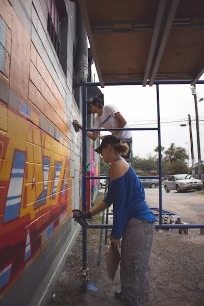 Triz (front) and her crew mate (back) work on their wall murals. Photo by Blue Hernandez.