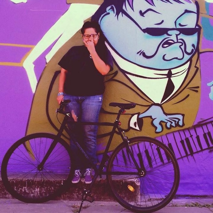 A photo of the photographer SzaGold standing with her bicycle. The background mural is by the local artist known as Nik Soupe. Courtesy Photo.