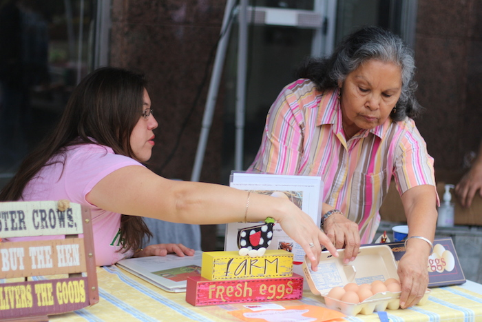 Gloria Flores and daughter-in-law, Henrietta Flores, place a carton of eggs onto their booth's table at the Main Plaza Farmers Market on Tuesday. Photo by Joan Vinson.