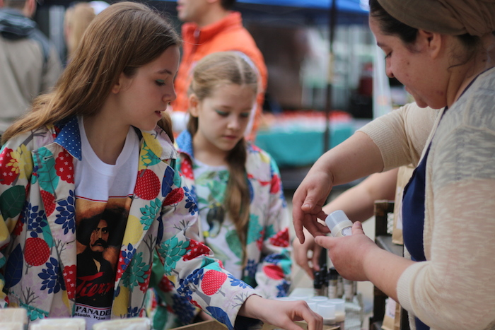 Soilnature shop owner Kelly Diaz lets sisters Lily and Caroline Watson sample her products. Photo by Joan Vinson.