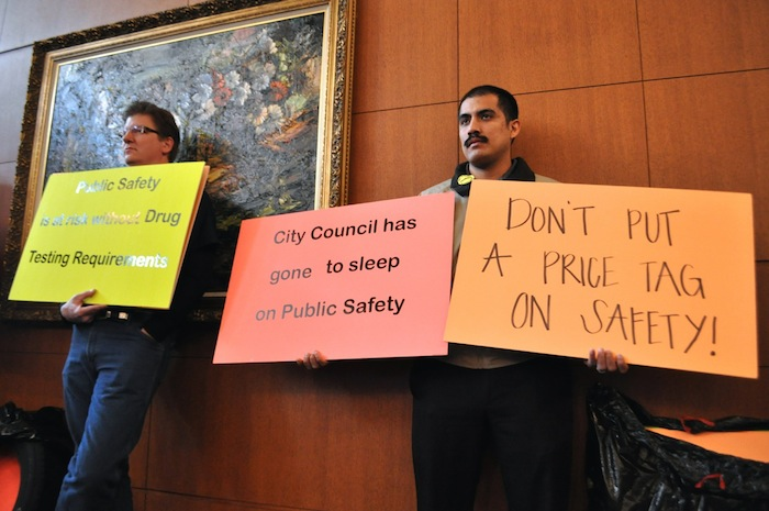 Mario Robledo,  dispatch manager for Yellow Cab San Antonio, holds signs in protest of the revisions to rideshare regulation. Photo by Iris Dimmick.