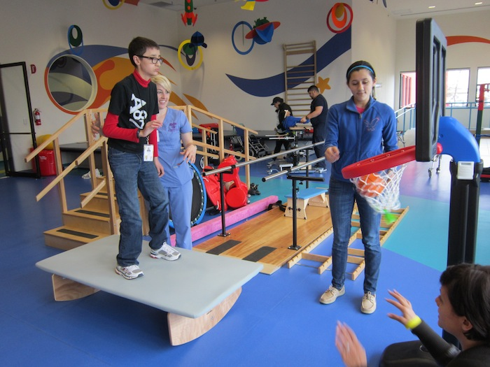 Ulises Murguia, 13, stands on a balancing platform to shoot baskets, supported by the center's physical therapy director Holly Hernandez and sister, Judith.