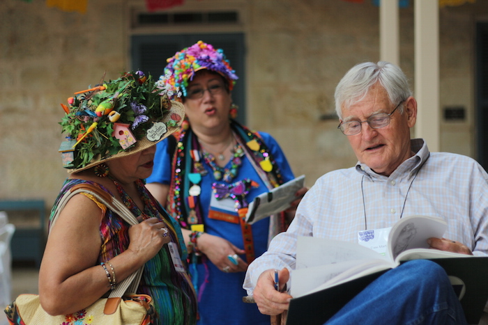 Dale Martin shows his artwork to attendees during the Fiesta Arts Fair. Photo by Joan Vinson.