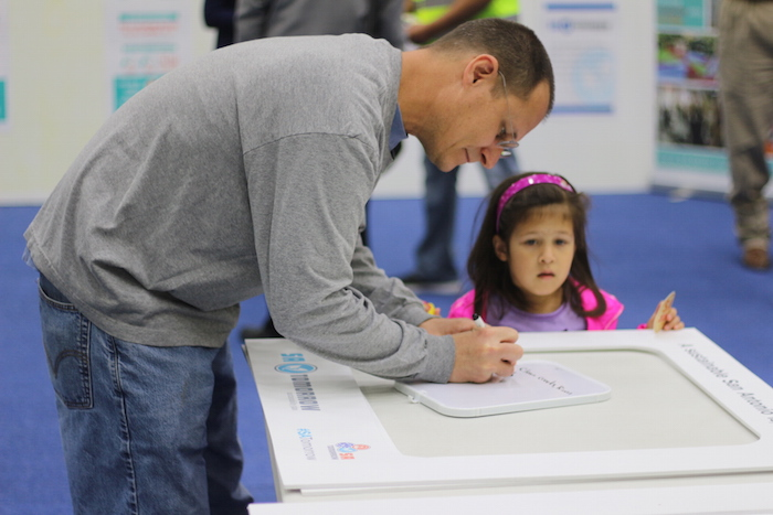 Brian Mast and daughter Evelyn provide feedback on a white board during the SA Tomorrow kickoff at the Alamo Convocation Center. Photo by Joan Vinson.