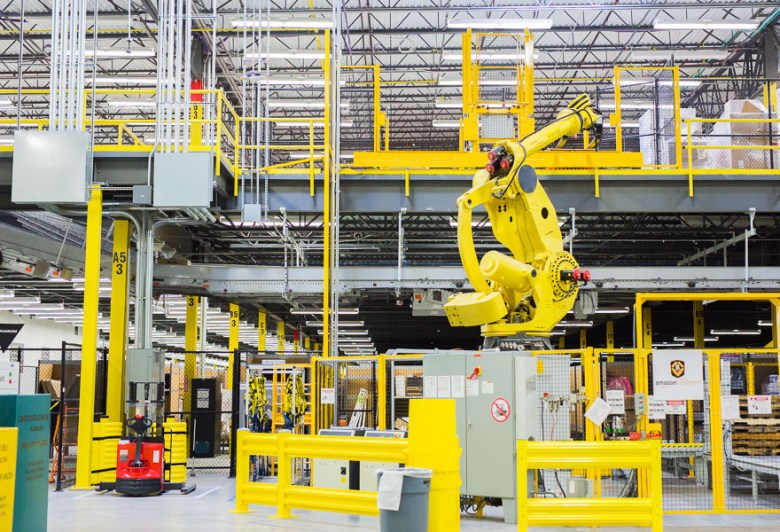"""The yellow armed robot """"Robo-Stow"""" at the Amazon Fulfillment Center.  Photo by Scott Ball."""