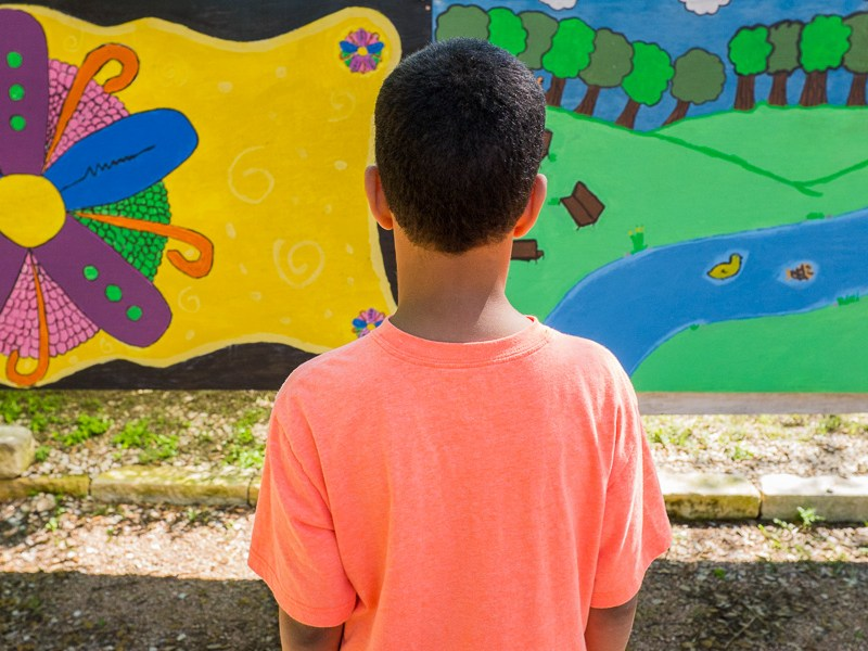 A child looks at a colorful mural during an outdoor activity at a playground designed with autistic needs in mind at the Autism Treatment Center of San Antonio. Photo by Scott Ball.