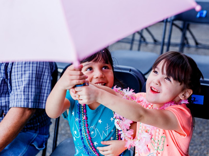 Two children play with an umbrella during the 2015 Battle of Flowers Parade in downtown San Antonio. Photo by Scott Ball.